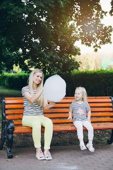 Мать и маленькая дочь едят сладкую вату