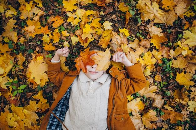 Милый мальчик гуляет и позирует в красочном осеннем парке