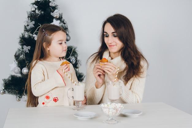 母と娘はおいしいカップケーキを食べる