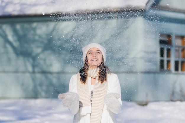 Девушка в шляпе и варежках бросает снег