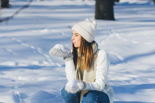 Девушка в шляпе и варежках дует снег