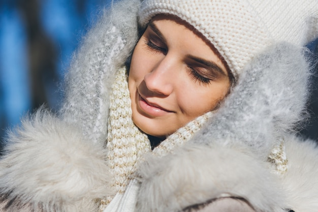 Девушка в шляпе и варежки улыбаются зимой
