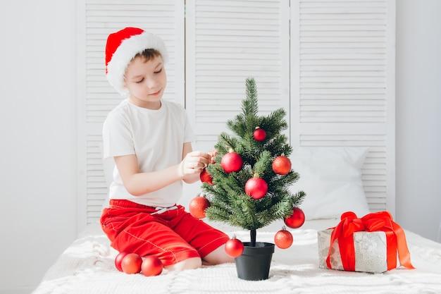 赤いサンタ帽子の少年は小さなクリスマスツリーのボールを飾る