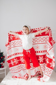 Мальчик прыгает на кровати, покрытой одеялом