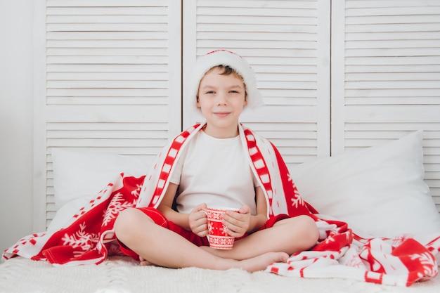 Мальчик пьет какао в кружке