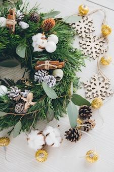 白い木製のテーブルに自家製のクリスマスリース