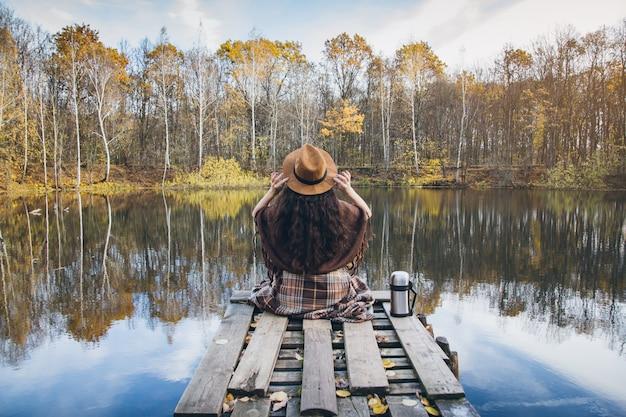 湖の上の木製の古い橋の上の少女