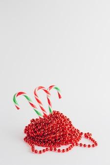 赤いクリスマスの花輪のキャンディー杖