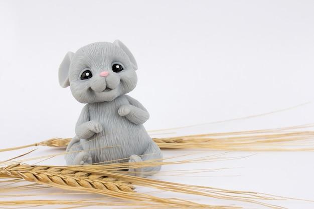 白の上に座って小麦の耳を持つマウス