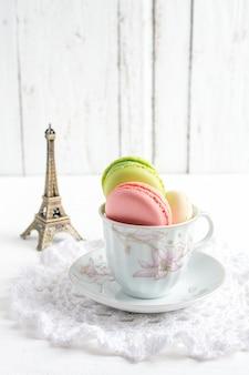 白い木製のカップでフランスのマカロン