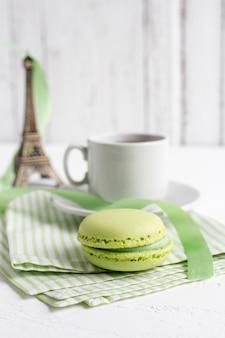 一杯のお茶と白い木製の緑のフランスのマカロン