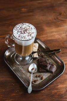 茶色の木製テーブルの上のガラスのカプチーノコーヒー