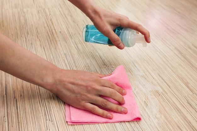 女性の手は布とスプレーで床を洗います。スプレークリーナー、洗浄コンセプトと積層床の洗浄。ハウスクリーニング