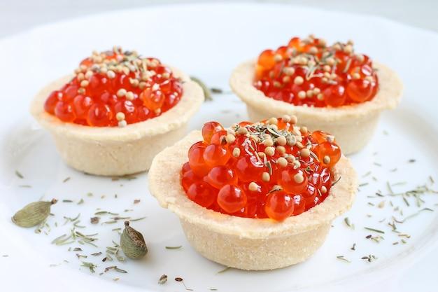 Красная икра в тарталетках на белой тарелке