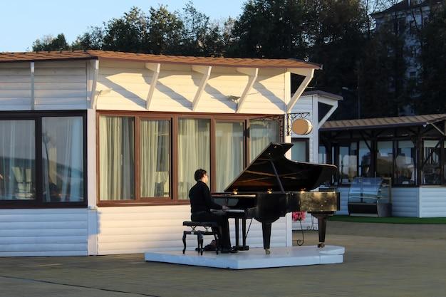 ヨーロッパの海でグランドピアノを演奏するストリートミュージシャン