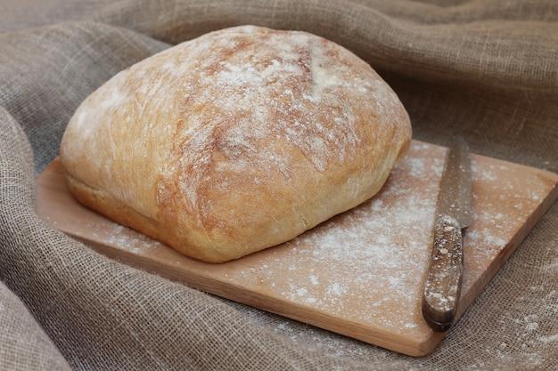 ナイフで木の板に焼きたてのパン。