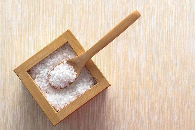 木のスプーンの上面の塩。木製テーブルの上のスパイス塩