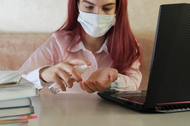 コロナウイルス。検疫。オンライントレーニング教育とフリーランスの仕事。ノートパソコンと女の子の消毒剤ジェルで手を掃除します。コロナウイルスの世界的流行。