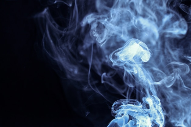 黒の背景に分離された抽象的な青い煙