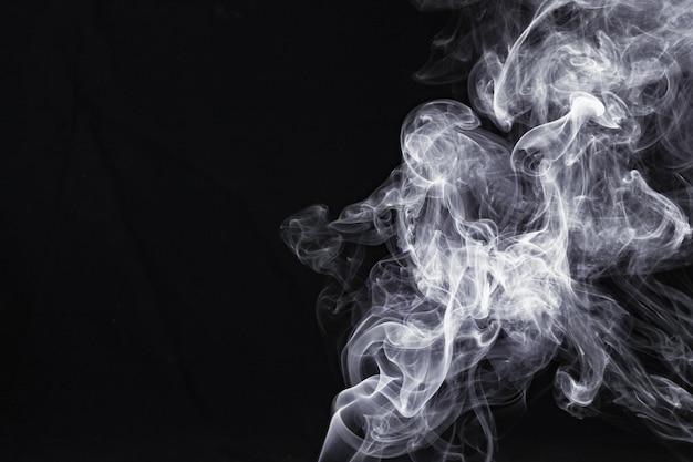 黒の背景に分離した抽象的な白い煙
