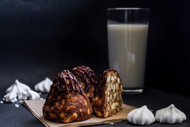 蟻塚チョコレートケーキミルクとメレンゲ、クローズアップ。暗い背景に