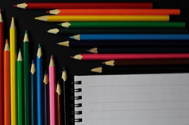 色鉛筆とノートブックの上面図。学用品