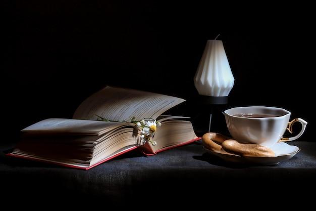 Чашка чая с открытой книгой и свеча крупным планом,