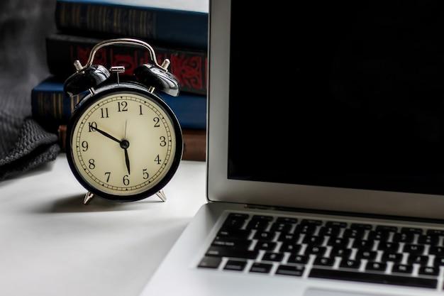Черный ретро будильник и ноутбук с книгами на темном фоне