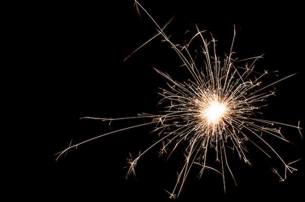 Один маленький новогодний бенгальский огонь на черном фоне.