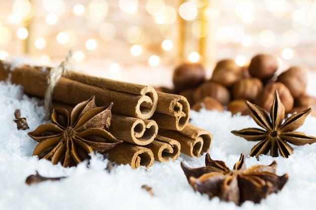 雪の上の伝統的なクリスマススパイスとナッツ。