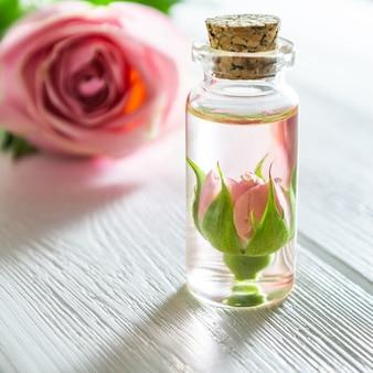 ローズのエッセンシャルオイルと白い木製のテーブルの上のバラの花。
