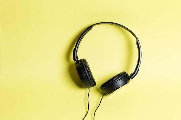 黄色の背景に黒のヘッドフォン