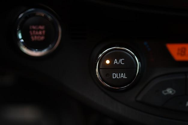 カーパネルのエアコンボタンが黒いパネルにクローズアップ