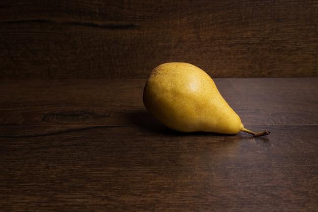 暗い茶色の背景に黄色の洋ナシ