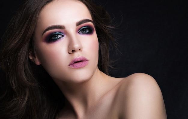 黒の背景に美しいブルネットの美しさの肖像画