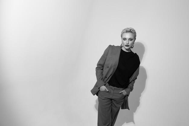 白い背景のスタジオでスーツを着たスタイリッシュな若い女性。ショートヘアカット。黒と白の写真。