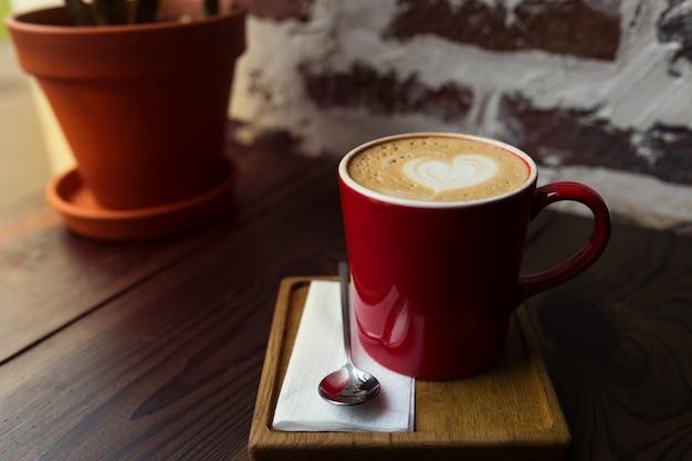 Капучино в красной кружке на деревянном столе
