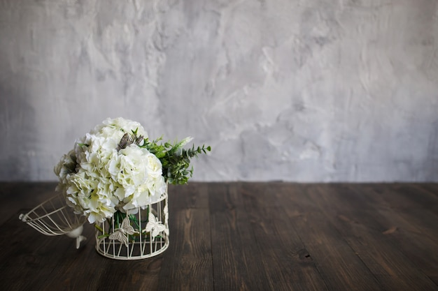 灰色の木の床の上に白いケージに白い花が立つ