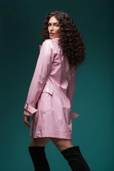Портрет брюнетки с вьющимися волосами в солнцезащитных очках и розовом лаковом пальто