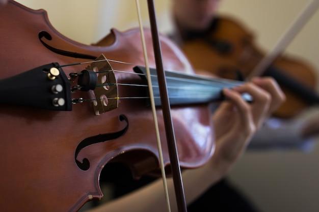 バイオリンを弾く少女。古いバイオリンのクローズアップ。