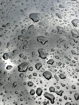 Капли воды на черном с отражением неба крупным планом