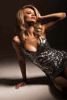黒のスタイリッシュなドレスでセクシーなブロンド