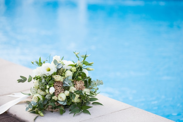 プールの境界線のクローズアップで結婚式ブライダルブーケ。