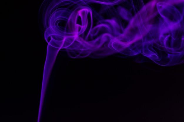 黒の背景にカラフルな煙のクローズアップ