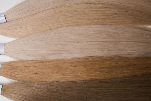 さまざまな色合いの髪。白い背景にクローズアップ。