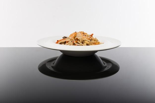 Лапша с морепродуктами на черном столе с белым