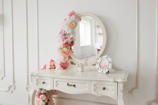 ラウンドミラーと花のビンテージスタイルの私室テーブル。白い明るい部屋。