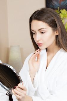 Красивая девушка смотрит в зеркало после косметической процедуры