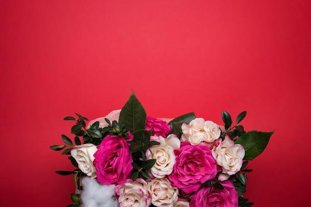 Красивые розы маленькой карзинке на красном фоне