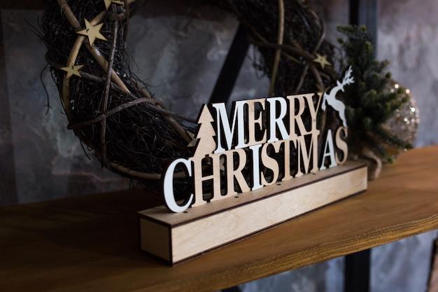メリークリスマスのクローズアップの碑文の看板が棚にあります。